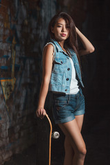 teen girl with skate board. Outdoors, urban lifestyle.