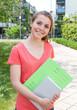 Lachende Studentin im roten Shirt auf dem Campus