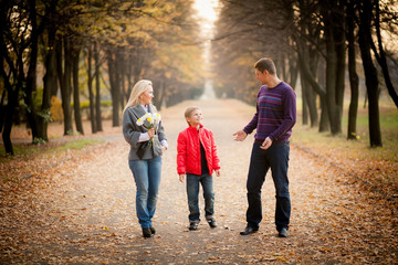 happy family walking in autumn park.  yellow leaves