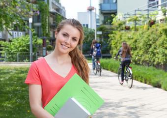 Studentin im roten Shirt steht auf dem Campus