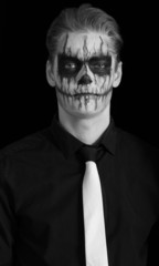 Portrait young man with skull makeup. Halloween face art