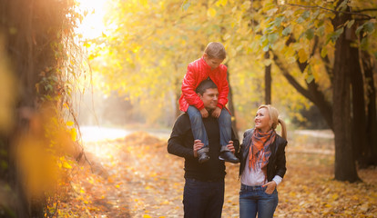happy family walking in autumn park.