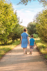 Grandmother and grandchild walking on a nature path