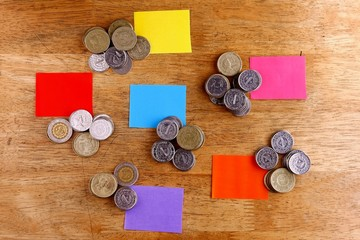 Different Stacks or piles of coins with colored paper tags