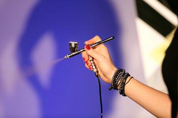 Airbrush in hand of make-up artist