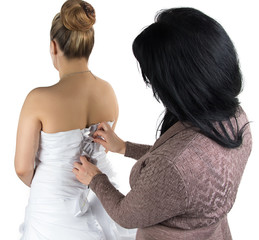 Image of bridesmade and bride in dress from back