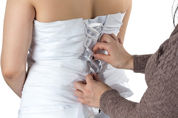 Photo of bride's back and bridesmade's hands