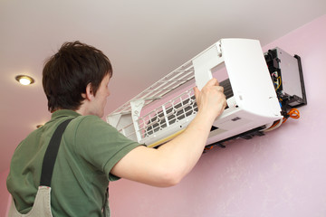 Worker installs grid on the air conditioner