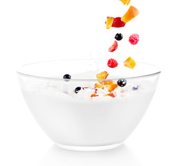 Delicious fresh berries and fruit falling into bowl of yogurt