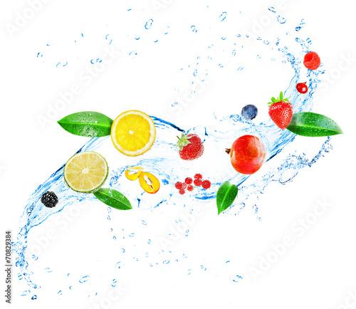 Leinwandbild Motiv Fresh fruit, berries and green leaves with water splash,
