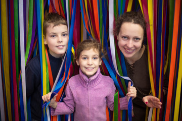 family of three against multi-colored ribbon labyrinth