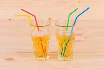 Two glasses full of apple juice.