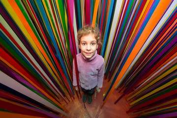 Beautiful little girl against the multi-colored ribbon labyrinth