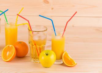Apple and orange juice on wood table.