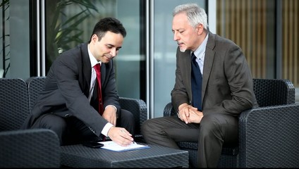People talking together while reading business documents