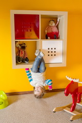 Little girl sitting upside down at inverted house