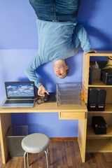 Man in jeans standing on ceiling under table with computer