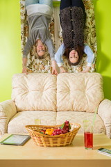 Two women stand upside down and hold on to sofa
