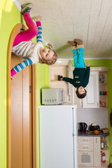 Two children upside down on ceiling of kitchen at inverted house