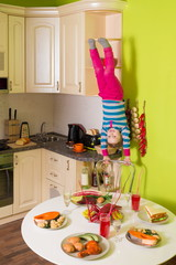 Little girl upside down holds chair in kitchen with table