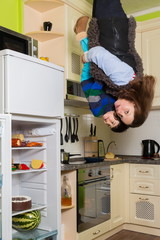 Mother with son stand upside down in kitchen with fridge