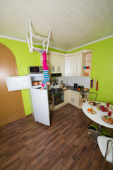 Little girl upside down holds fridge in kitchen with table