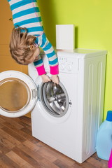 Girl hanging upside down holding washing machine