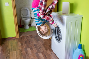 Girl upside down holding washing machine at inverted house
