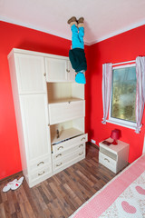 Little boy standing on ceiling next to closet at inverted house