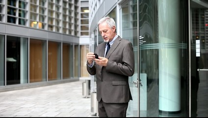 Businessman walking out from an office and adjusting his tie