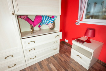 Little girl upside down in the closet at inverted house