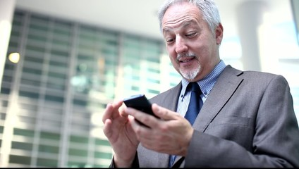 Senior businessman using his smartphone