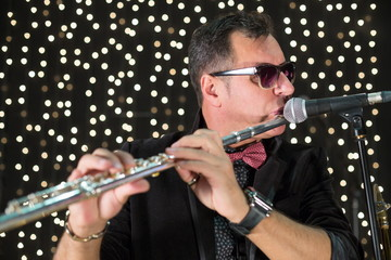 Musician with flute in a bow tie playing in a club