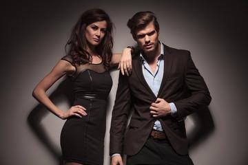 elegant couple leaning on a dark grey wall