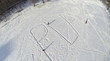 Aerial view to children drawing big word PLAY on snow