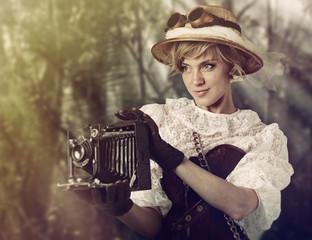 Beautiful woman with retro camera in the jungle