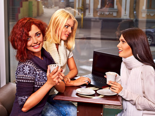 Women at laptop drinking cocktail in a cafe.