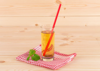 Apple juice and slices on wooden background.