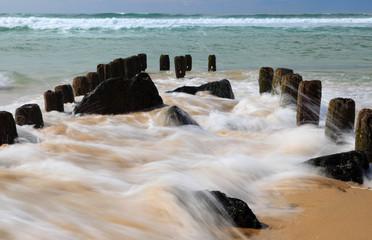 Felsen, Pfähle und wellen am Strand