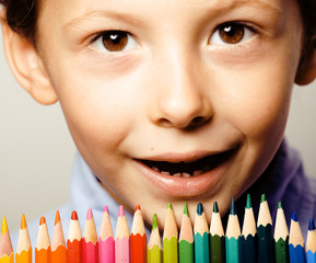 little cute boy with color pencils close up smiling
