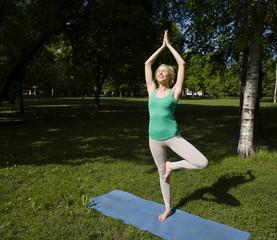 blonde girl doing yoga in park
