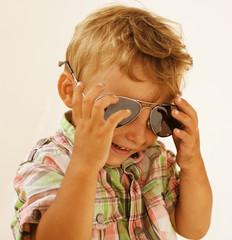 Little boy in sunglasses against white background