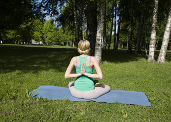 blonde girl doing yoga in park