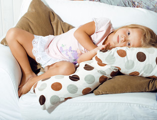 little cute blonde girl playing at home with pillows