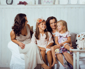 Mature sisters twins at home with little daughter, happy family