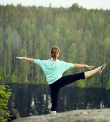 Cute girl making gymnastic on the top of mountain, lake down.