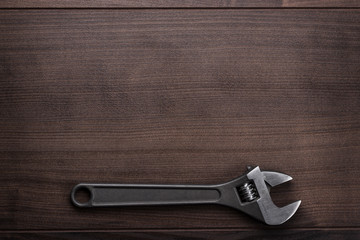 adjustable wrench on the wooden background