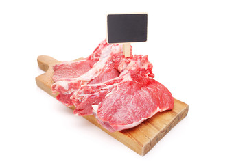 Raw beefsteaks on a cutting board with a price tag