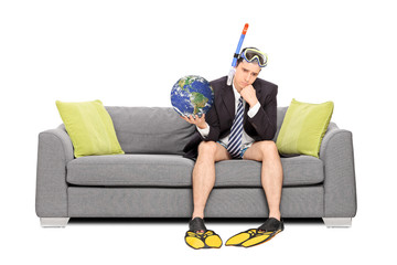 Sad businessman holding the earth and sitting on sofa