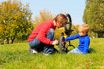 father and son fixing bike outdoors